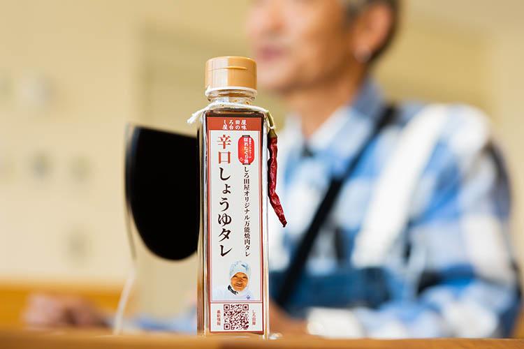 ボトルを持っている  中程度の精度で自動的に生成された説明